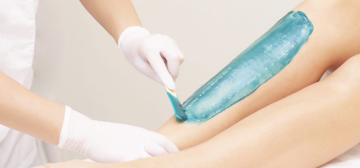 azulene depilation. wax hair removal, shugaring. concept of smooth skin without hair. azulene of green color. the master puts azulene on the girls legs