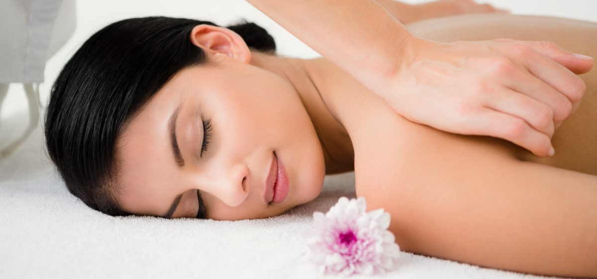 Pretty brunette enjoying a massage with flower at health spa